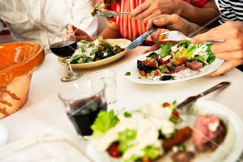 Dinner party with salad and red wine, close-up, Sweden.