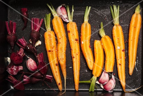 Carrots, garlic and beetroot on a baking tray