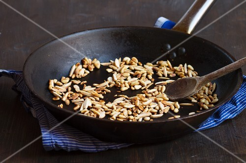 Toasted almonds and pine nuts in a black frying pan