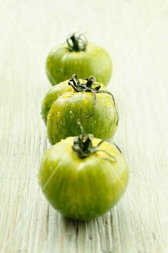 Three green tomatoes with water droplets