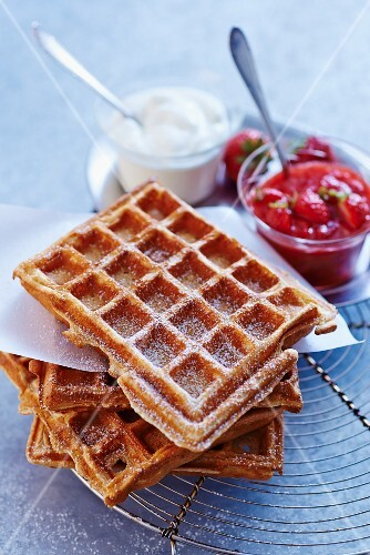 A stack of waffles with icing sugar, strawberry compote and cream