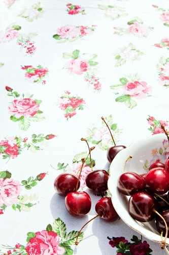 Red cherries in an old bowl on a rose-patterned cloth