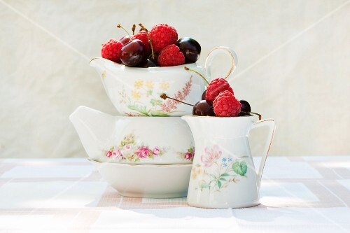 Raspberries and cherries in old milk jugs
