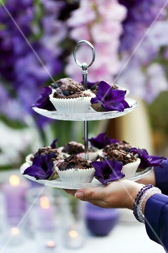 Chocolate muffins and purple flowers on cake stand