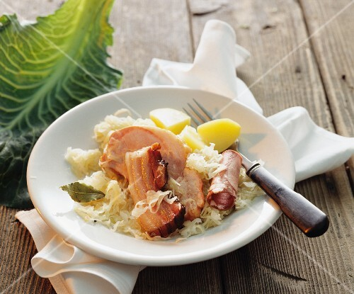 A meat platter with sauerkraut and potatoes