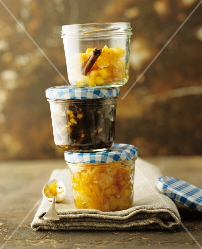 Three different chutneys in stacked jars