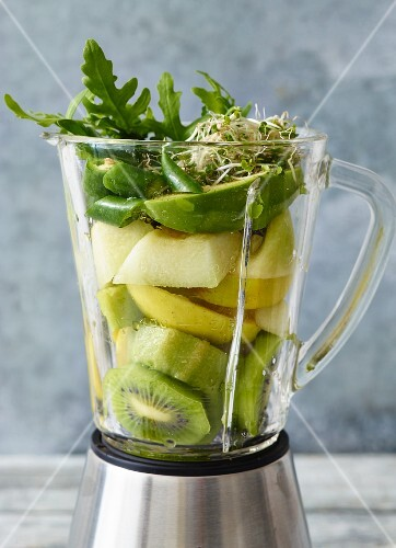 Ingredients for basil & avocado smoothie and for kiwi & cucumber smoothie, in a blender