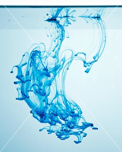 Blue ink dripping into water