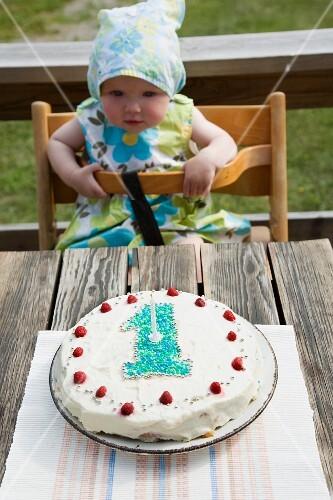 A baby looking at her birthdaycake, Sweden.