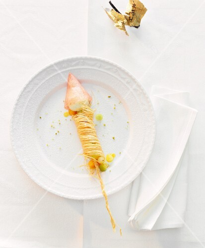 The remnants of a king prawn with vermicelli on a plate