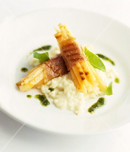 Grilled white asparagus wrapped in ham, on risotto