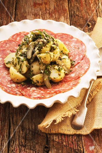 Potato salad with herb dressing, served on slices of salami