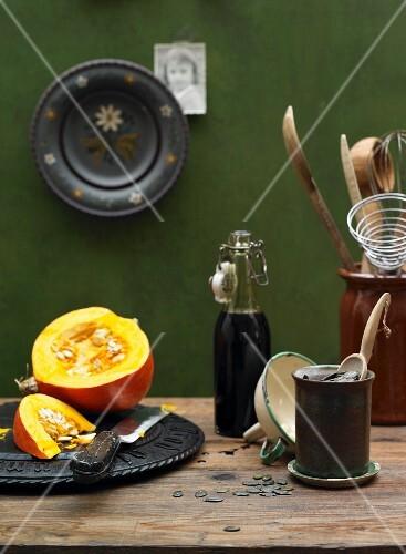 An arrangement of pumpkin seed oil, a pumpkin and pumpkin seeds