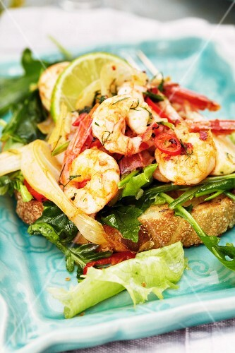 Chilli prawns with rocket and lime wedges on toast