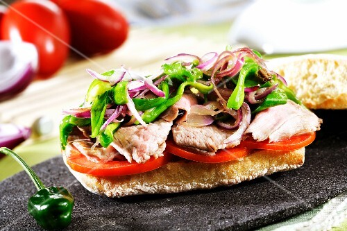 Toast topped with pork, tomatoes, peppers and onions
