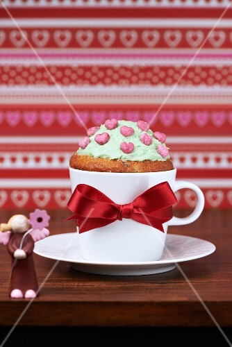 A guardian angel cupcake with butter cream and heart decorations in a coffee cup