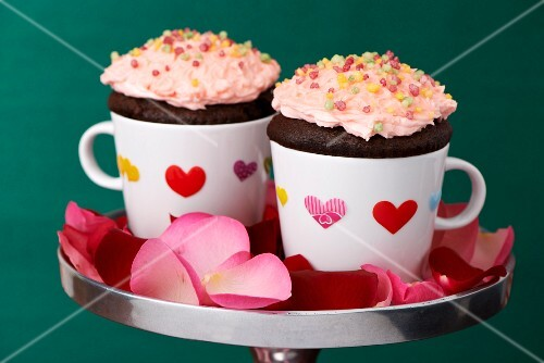 Chocolate cupcakes in coffee cups with heart stickers and rose petals