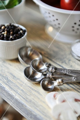 Assorted silver measuring spoons, peppercorns and sliced mushrooms