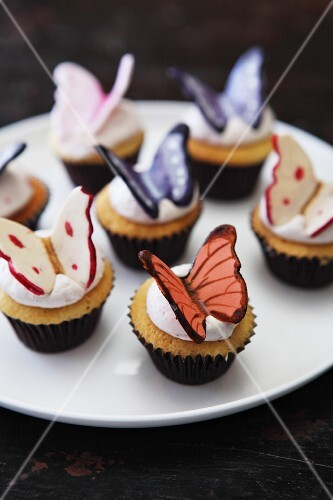 Vanilla cupcakes with cream icing and chocolate butterflies