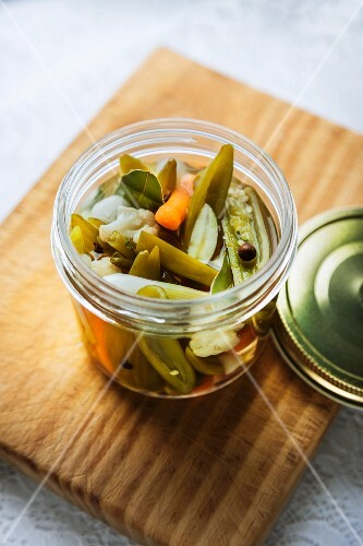 Vegetables pickled in vinegar, in an open screw-top jar