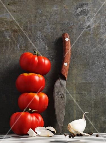 Beef tomatoes with a sharp knife and a clove of garlic