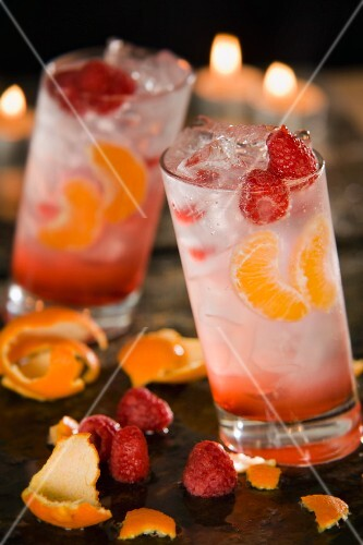 Two fruity cocktails with raspberries and mandarins