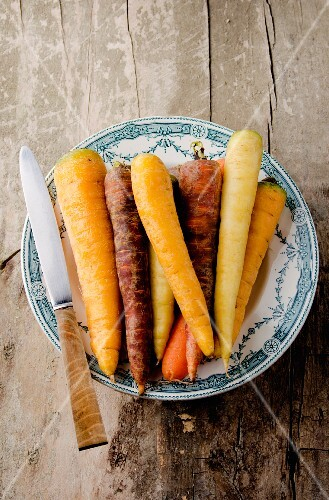 Assorted varieties of carrot on an old plate, with a knife