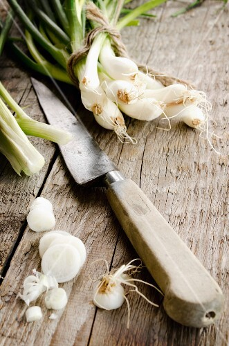 Spring onions, partly slices, with a knife, on a wooden surface