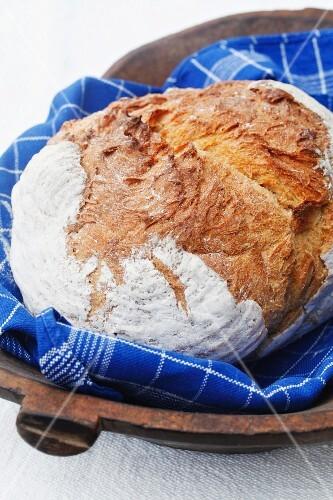 Spelt bread on a tea towel in a wooden bowl