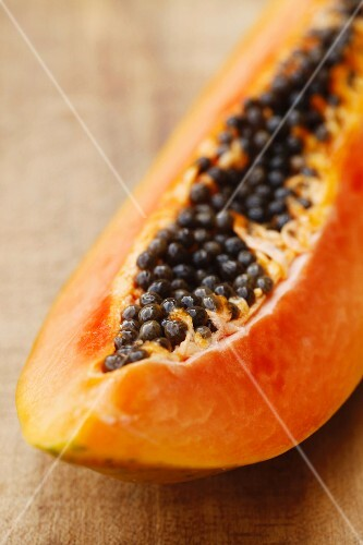 Segment of papaya on a wooden board