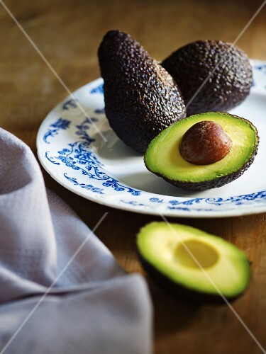 Whole and halved avocado