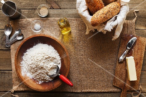 Overhead view of ingredients for making bread - flour, yeast, oil, butter, salt and water