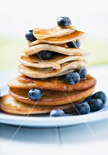 A Stack of Pancakes with Fresh Blueberries and a Syrup
