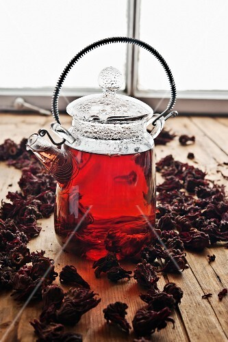 Hibiscus tea in a glass teapot surrounded by hibiscus flowers