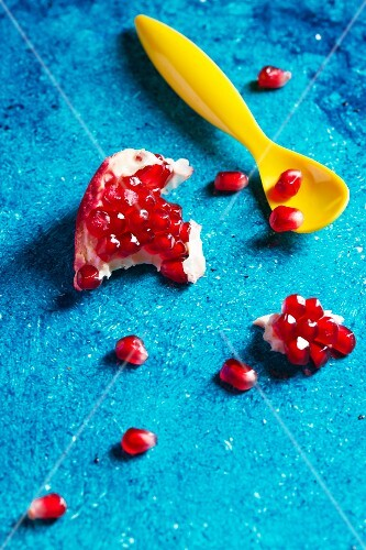 A chunk of pomegranate and pomegranate seeds on a turquoise surface with a yellow spoon