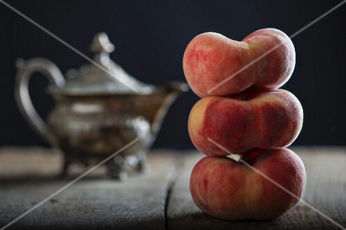 Three stacked vineyard peaches in front of a teapot