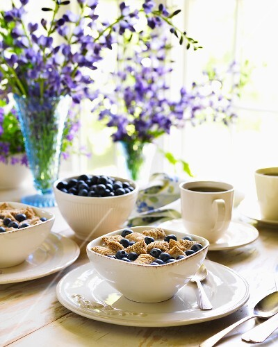 A Breakfast Table Set of Shreded Wheat with Blueberries and Coffee