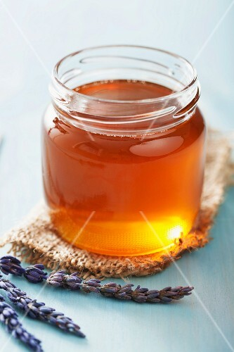 A jar of honey and lavender flowers