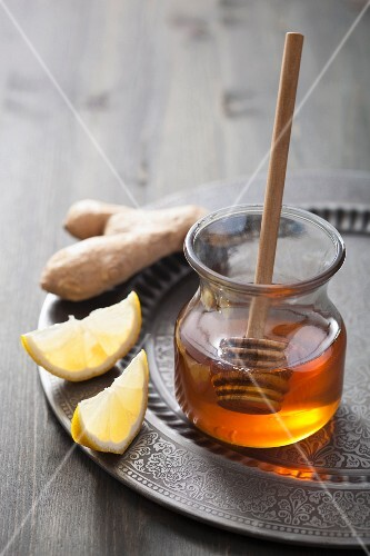 A jar of honey, lemon wedges and ginger