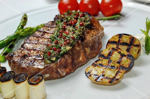 Grilled beef steak with herb butter and vegetables