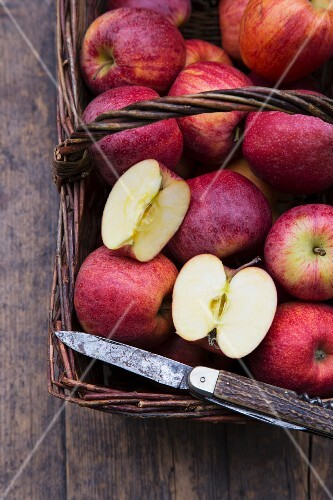 Apples (Royal Gala) in a basket with a knife on a wooden table