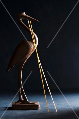 A wooden bird with two strands of dried spaghetti