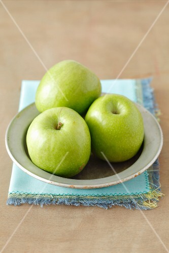 Three green apples on a plate
