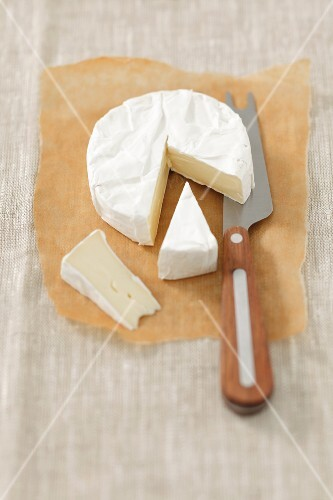 Camembert on grease-proof paper, partly sliced