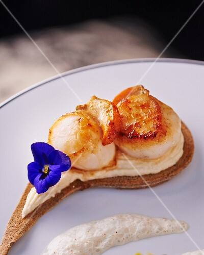 A pancake topped with fried scallops and a pansy
