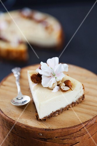 A slice of vanilla cheesecake with smoked cream cheese and hazelnuts