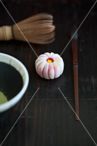 A wagashi chrysanthemum (kiku), a tea whisk, a matcha spoon and matcha tea