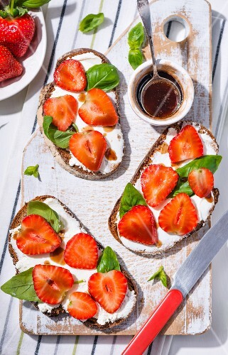 Slices of bread topped with cream cheese, strawberries, balsamic vinegar and basil