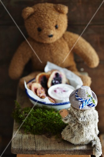 Mini pancakes with berries and yoghurt sauce in a bowl surrounded by stuffed animals