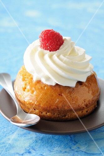 Rum baba with cream and a raspberry